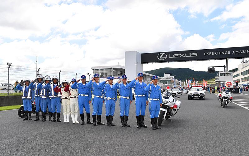 大分県警察の白バイとパトロールカーが、第6戦オートポリスの決勝レース前にGTマシンとパレードを行い交通安全を呼びかけるの画像